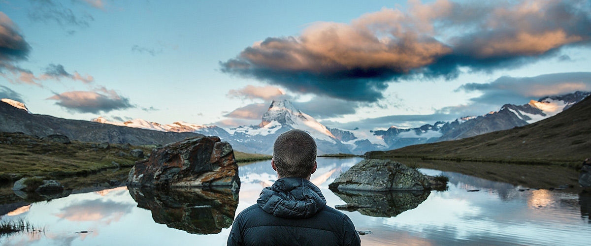 man looking at lake and mountains in the distance